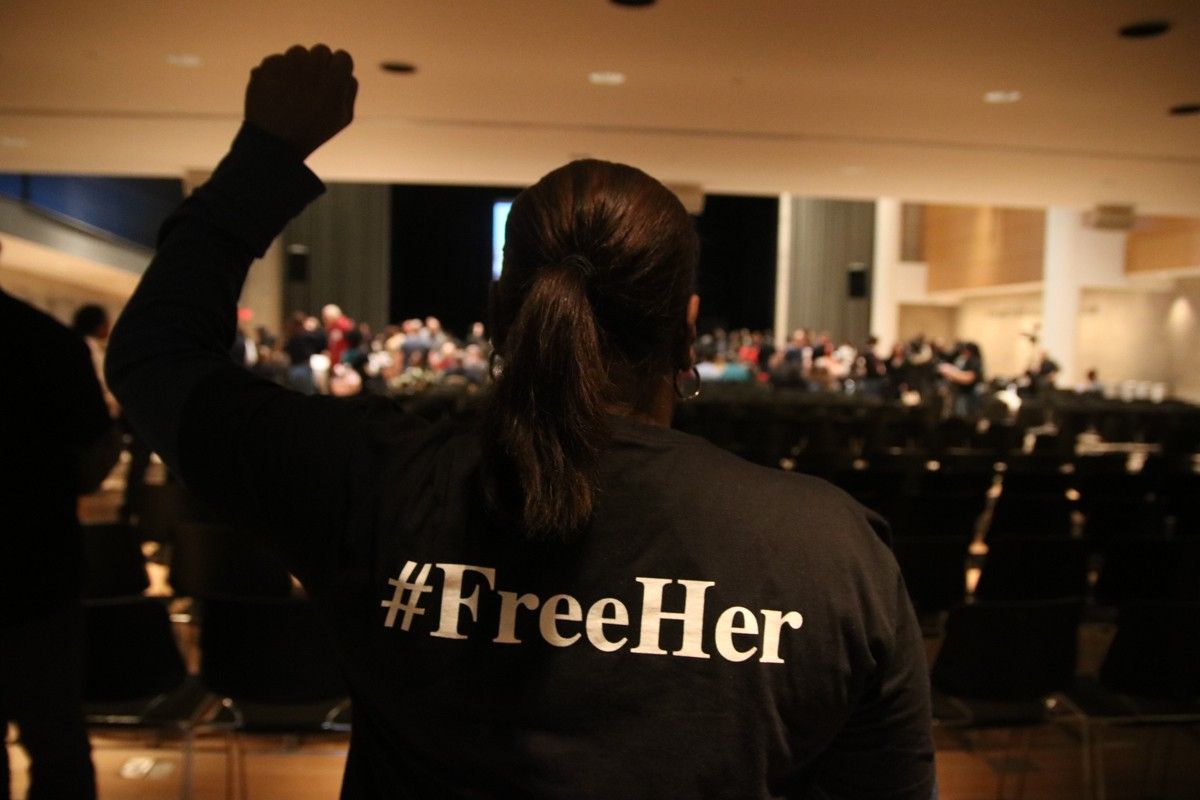 Woman with fist in the air and #FreeHer on the back of her jacket