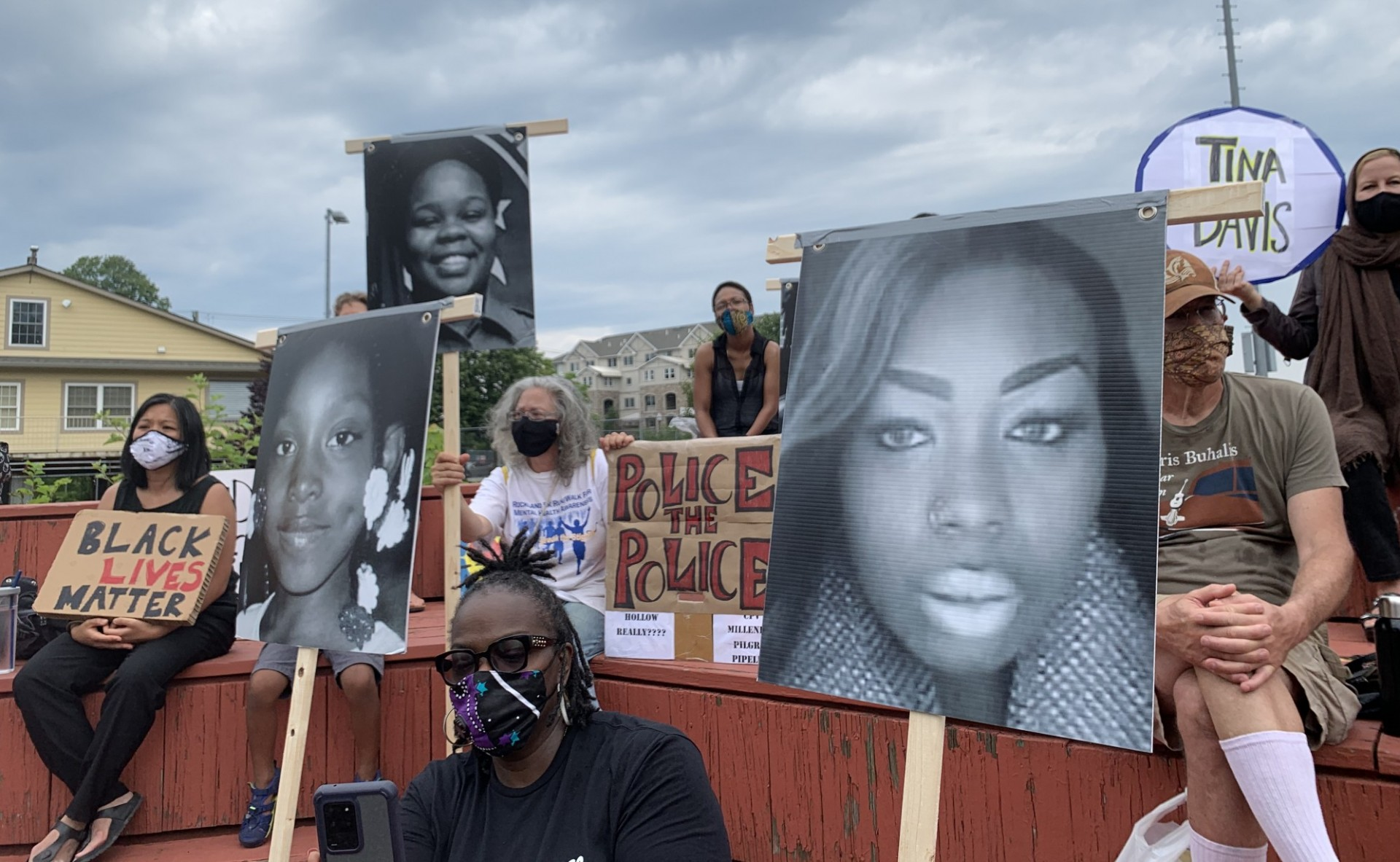 Rally in Rockland County with participants holding photos of women who have been killed by police
